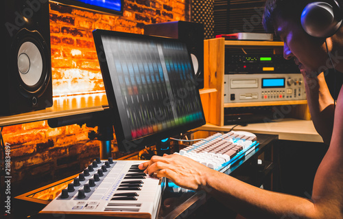 young asian male composer playing midi keyboard for arranging a song on computer in home studio - 218834897