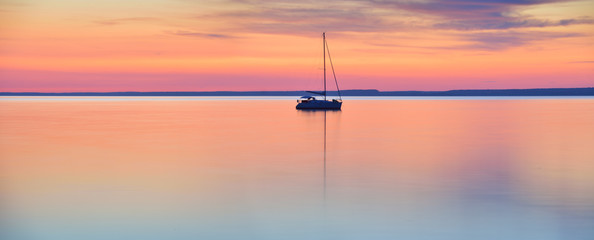 The world at rest - sailing boat in calm lake at sunset