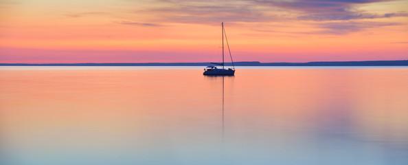 Svijet u mirovanju - jedrilica u mirnom jezeru za zalaska sunca