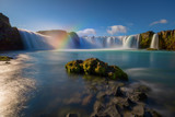 Fototapeta Tęcza - Iceland's Godafoss waterfall on a clear, sunny day.  The falls creating streams of light through the water and a rainbow