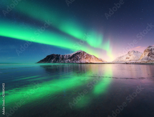 Photo sur Aluminium Aurore polaire Northern lights in Lofoten islands, Norway. Green Aurora borealis. Starry sky with polar lights. Night winter landscape with aurora, sea with sky reflection, rocks, beach and snowy mountains. Travel
