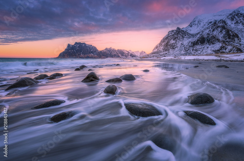Obraz Beautiful sandy beach with stones in blurred water, colorful cloudy pink sky and snowy mountains at sunset. Utakleiv beach, Lofoten islands, Norway. Winter landscape with sea, waves, rocks at dusk - fototapety do salonu