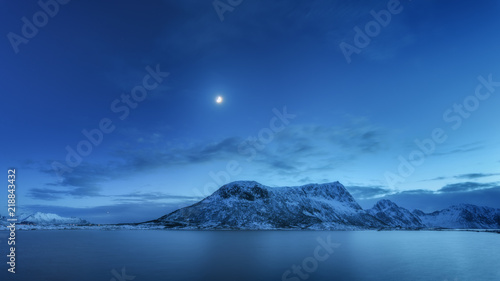 Foto op Plexiglas Noord Europa Snow covered mountains against blue sky with clouds and moon in winter at night in Lofoten islands, Norway. Arctic landscape with sea, snowy rocks, moonlight, reflection in water. Beautiful fjord