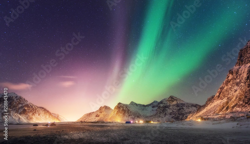 Poster Aurore polaire Green and purple aurora borealis over snowy mountains. Northern lights in Lofoten islands, Norway. Starry sky with polar lights. Night winter landscape with aurora, high rocks, beach. Travel. Nature