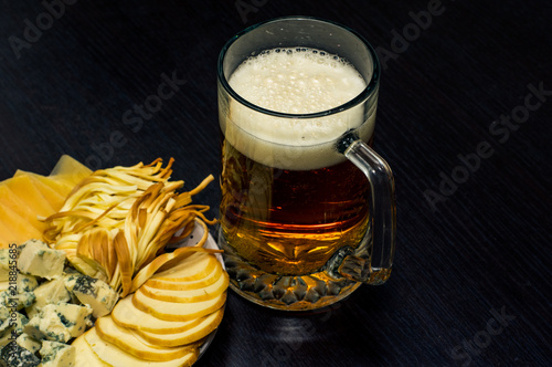 Photo  a beer mug and a plate with several kinds of cheese on the table