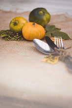 Seasonal Table Setting With Small Pumpkins And Yellow And Green Leaves