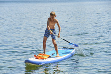 Paddle Boarder. Child Boy Paddling On Stand Up Paddleboard. Healthy Lifestyle. Water Sport, SUP Surfing Tour In Adventure Camp On Active Family Summer Beach Vacation.