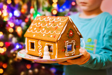 Christmas Gingerbread House In Children's Hands Close-up Against The Backdrop Of Lights In The Festive Living Room. Baking And Cooking With Children For Xmas At Home.