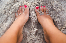 Young Tanned Woman With Red Pedicure Digs Feet Into White Sand On A Beach
