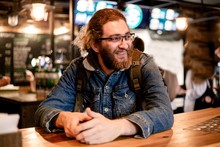 Hairy Male Traveler In A Denim Jacket At A Cafe