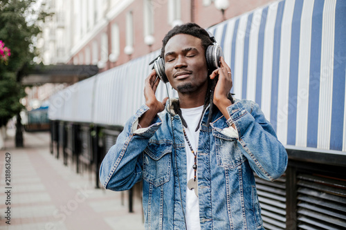 Deurstickers Muziekwinkel African man in denim jacket listening to music with headphones on the street