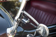 closeup of vintage automobile in black with red leather upholstery and lots of chrome
