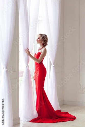 Fotografie, Obraz  Young adult elegant woman with perfect makeup and red long dress, standing near window holding curtains and looking outside