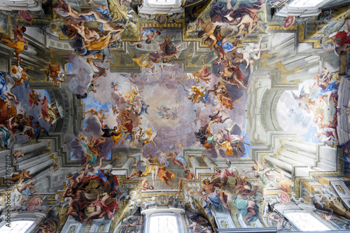 Fototapeta Paintings and frescos on the ceiling of a catholic Church of St