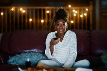 African American Woman In Pajamas Staying Up Late At Night Eating Pizza And Watching Tv