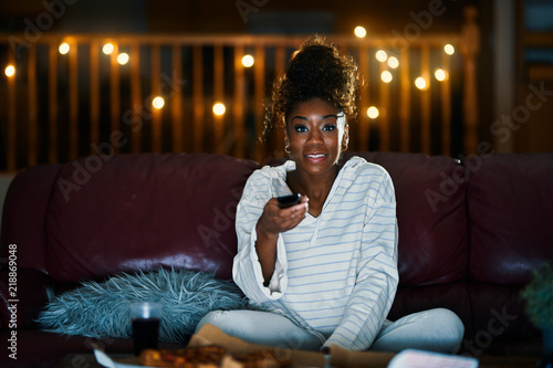 Fotografie, Obraz  african american woman in pajamas staying up late at night eating pizza and watc