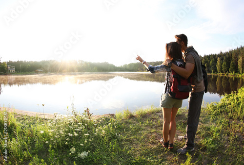 Young couple on shore of beautiful lake, wide-angle lens effect. Camping season