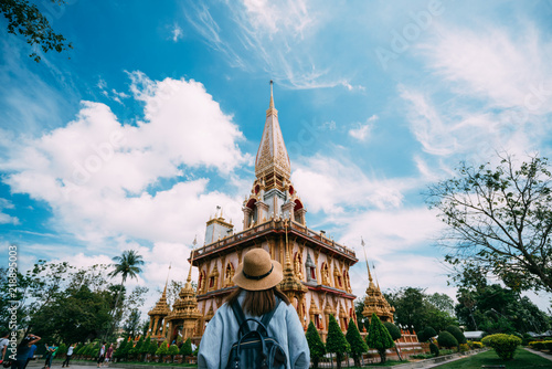 Spoed Foto op Canvas Bedehuis Young woman traveler with backpack traveling into beautiful pagoda in Wat Chalong or Chalong temple at Phuket town, Thailand. It's most popular thai temple in Phuket Thailand.
