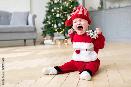 Cute baby in red Christmas costume sitting on floor of stylish room and crying Canvas