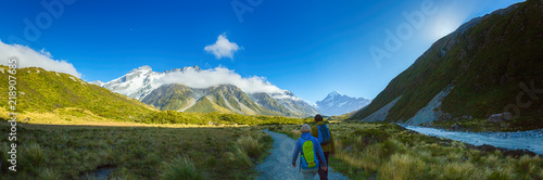 Photo Stands Europa Panorama of Couple hiking on Hooker Valley Track in South island New Zealand, Mount cook national park, summertime