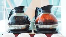Coffee Pot And Tea Pot  On Hot Stove.