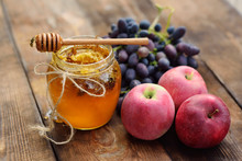 The Wasps Fly Around The Jar With Honey, Grapes And Apples On A Wooden Background