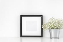 Elegant Black Square Frame Mockup In Interior. Frame Mock-Up Poster Or Photo Frame And Delicate Flowers In Vase Near White Wall. Desk Space, Copy Space. Background. Poster Mockup