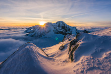 Stunning Sunset Or Sunrise In Winter Alpine Like Snow Landscape. Inversion, Sun Star Peaking Behind High Rocky And Icy Summit. Purple, Pink, Blue And Orange Colors. Ladovy Stit In Winter High Tatras.