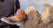 Wanderschuhe die über der Schulter eines Wanderers baumelnd hängen vor einer Bergkulisse.