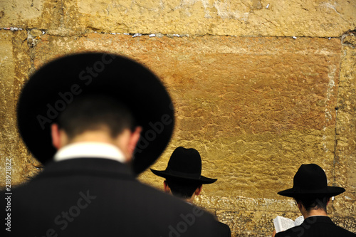 Orthodox Jewish men pray at the western wailing wall  in Jerusalem old city Israel