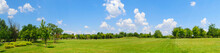 Panorama Of Green Lawn Field With Trees In The Background. Park At Mogosoaia Palace Near Bucharest, Romania.