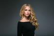 Leinwandbild Motiv Blonde hairstyle woman beauty with long curly blonde hair over dark background