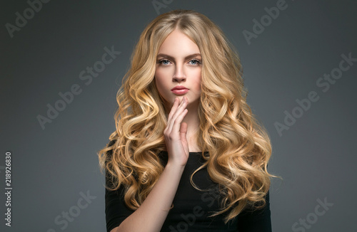 Blonde hairstyle woman beauty with long curly blonde hair over dark background Fototapete