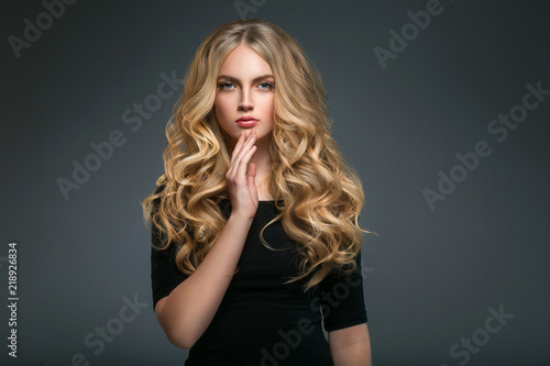 Obraz na plátně  Blonde hairstyle woman beauty with long curly blonde hair over dark background