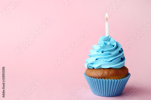 Stampa su Tela  Tasty cupcake with candle on pink background