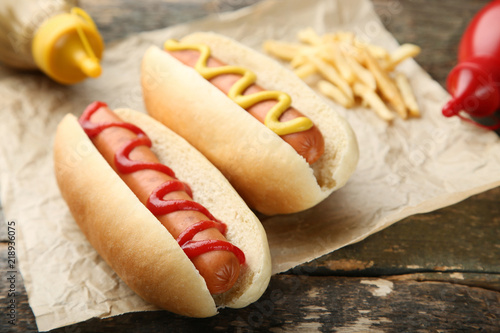 Fotografia, Obraz Hot dogs with mustard and ketchup on wooden table
