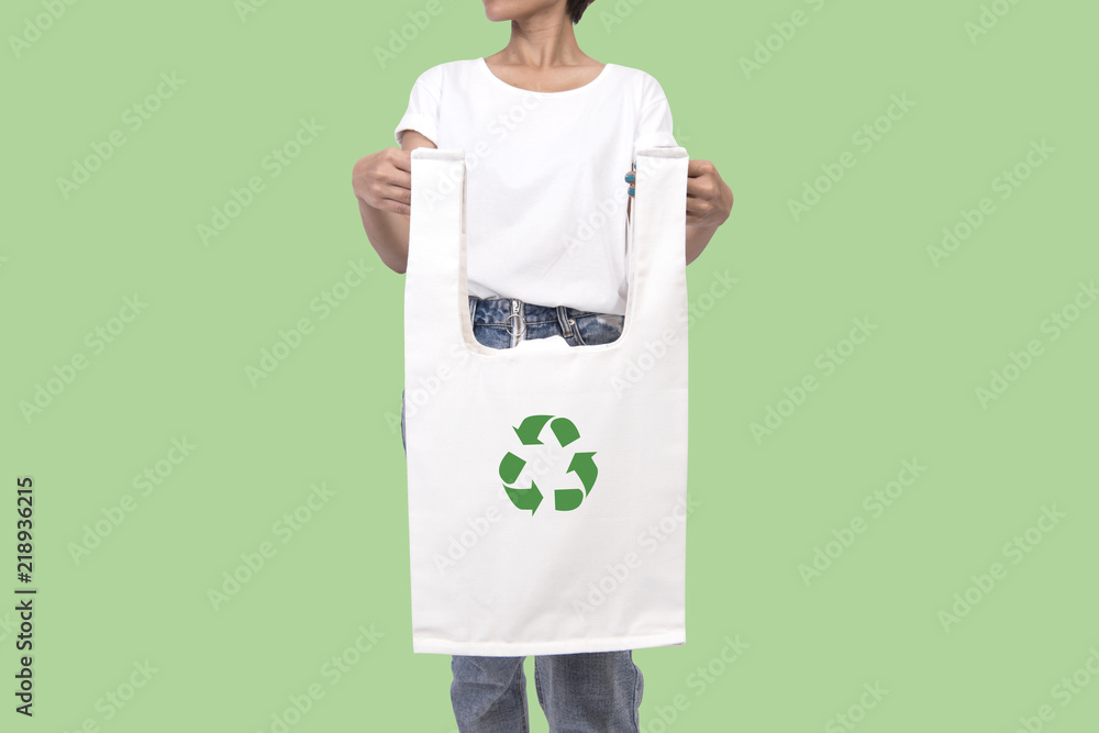 Fototapeta Girl is holding bag canvas fabric with recycle symbol isolated on green background. eco and save the earth concept.