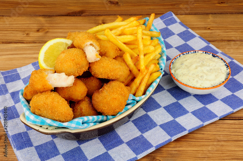 Scampi and French fries meal with tartar sauce on a wooden background