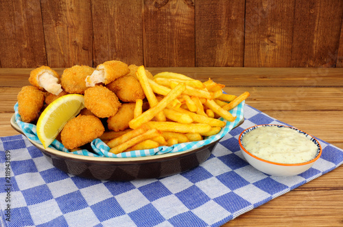 Foto op Aluminium Buffet, Bar Scampi and French fries meal with tartar sauce on a wooden background