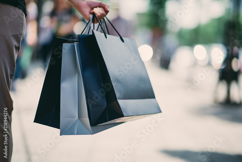 Fototapeta Close up of woman`s hand holding shopping bags while walking on the street. obraz