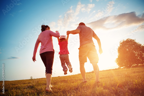 Obraz girl with mother and father holding hands on the nature. Child with parents outdoors - fototapety do salonu