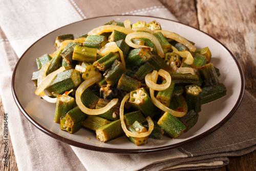 Fototapeta Vegan cuisine: spicy okra fried with onion close-up on a plate. horizontal obraz