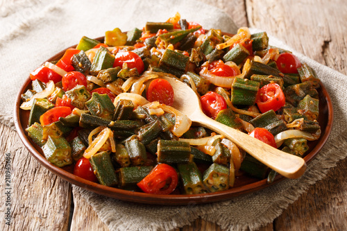 Serve Organic okra with tomatoes and onion close-up on a plate on the table. horizontal, rustic style