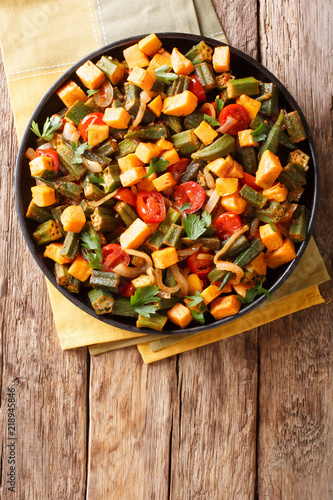 Traditional recipe ragout from okra, sweet potato, tomatoes, onions and herbs close-up on a plate. Vertical top view