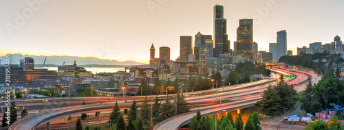 Garden Poster Brown Panoramic view Seattle skylines and rush hour traffic on highway I-90 and I-5 interchange. Nearby density of homeless tents, tiny shelter in trees foreground on the left. Problem of urban life concept
