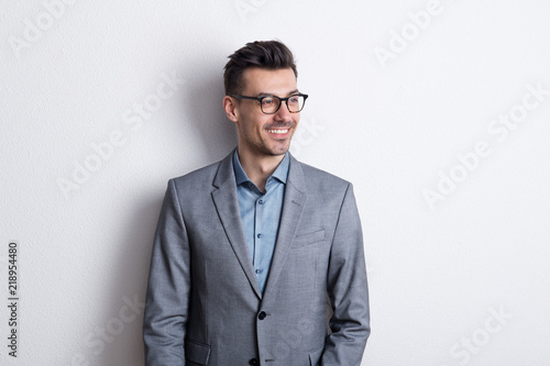 Obraz Portrait of a cheerful young man with glasses in a studio. - fototapety do salonu