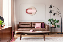 Real Photo Of Wooden Coffee Table Placed On Carpet In Bright Sitting Room Interior With Leather Brown Couch, Modern Clock On Wall, Metal Lamp And Window With Drapes