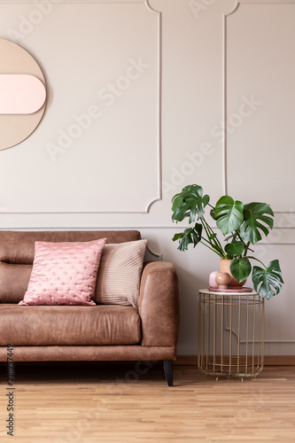 Fotografía  Real photo of end table with decor and fresh plant placed next to leather sofa w