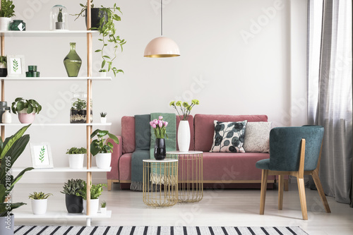 Real photo of a green armchair, pink couch, gold tables with ...