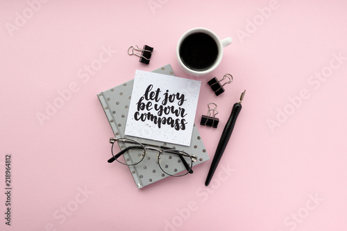 Photo  Minimal composition with notepad, calligraphic pen, glasses, mug of coffee, black paper clamps on a pink background